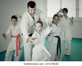 Young children doing karate kicks with male coach during karate class