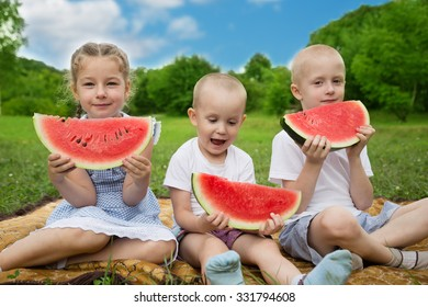 Young children eating watermelon sitting in a park.