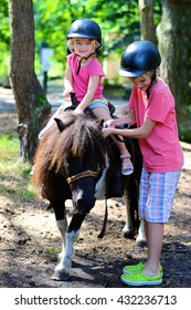 Young children enjoying horse back riding activity. Group of school age kids taking care about their pony and learning how to feed the animal. Summer camp for active holidays.