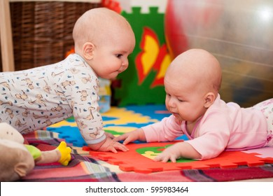 Young children, girl and boy, brother and sister sitting on the floor in the nursery and play with toys