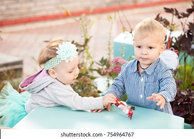 Young children, girl and boy, brother and sister sitting on the floor in the nursery and play with toys or eat chokolate