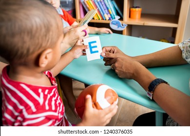 Young children learning the English alphabet with their parents