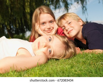 Young children lying on grass, close up