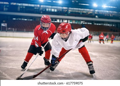 young children play ice hockey