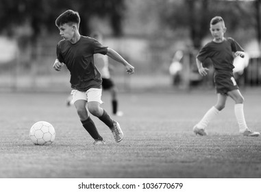 Young children players match on soccer field - black and white photography