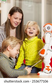 Young children playing with humanoid robot during school time