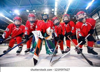 young children playing ice hockey on the rink