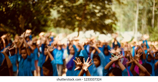 Young children raising their hands in a school assembly time