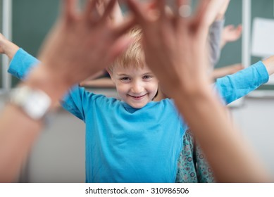 Young children rejoicing as they play at school with a view through a kids hands of a smiling young boy