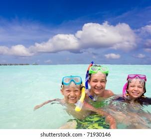 Young children snorkeling in the ocean.