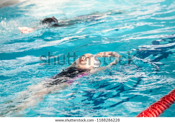 Young children swimming backstroke in pool at lane