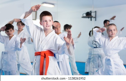 Young children training new moves during karate class