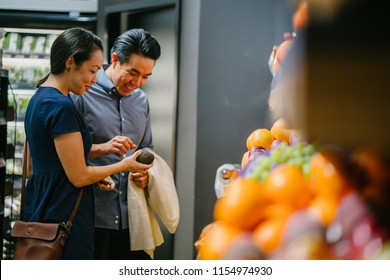 A young Chinese Asian couple stand next to one another as they pick fruit and vegetables (fresh organic produce) at a supermarket together. They are young, attractive and are smiling as they shop.