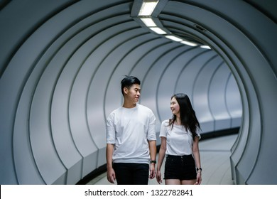 A young Chinese Asian couple walk together in an underground tunnel. They are both students and are on a date together on the weekend. The boy and girl are smiling and laughing happily.