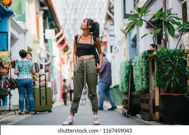 A young Chinese Asian millennial teenager girl walks along the colorful and trendy Haji Lane, a trendy street in Bugis, Singapore. The teen is sporty and wearing street clothing to explore.