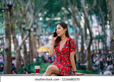 A young Chinese Asian student girl is sitting on a ledge in a park and speaking on her smartphone. She is wearing a red dress and is smiling as she takes her phone call.