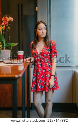 d3fef180ebb9 A young Chinese Asian student girl in a red dress enjoys a cup of hot coffee