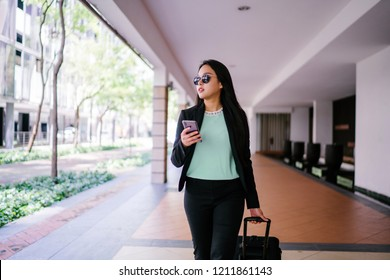 A young Chinese Asian woman pulls a luggage suitcase on wheels along behind her as she walks to the pickup point for the ride she booked on the ride-hailing app  during the day. She is wearing a suit.