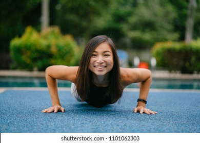 A young Chinese Asian woman s in a yoga pose (high plank) and she is smiling. The young woman is athletic, tanned and fit.