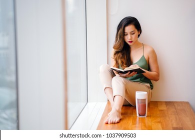 A young Chinese Asian woman sits by a window in her apartment in the morning and reads a book while she drinks a healthy shake. She is about to start her day and is enjoying a quiet moment.