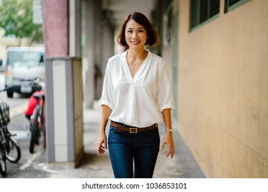 A young Chinese Asian woman walks along a corridor in Asia. She is dressed smartly in business casual, has bobbed hair and is smiling as she strolls down the corridor.