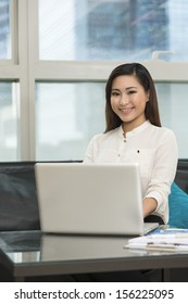 Young Chinese business woman working from home. Asian female using a laptop.