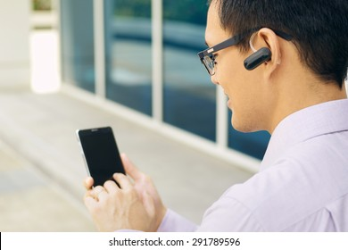 Young chinese businessman typing phone number on smartphone and talking with bluetooth headset device