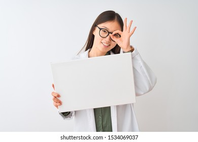 Young chinese dooctor woman wearing glasses holding banner over isolated white background with happy face smiling doing ok sign with hand on eye looking through fingers