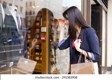 young chinese girl looking in a shop window