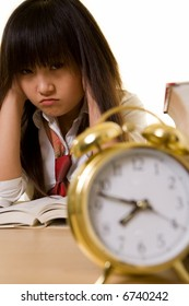 Young Chinese girl wearing school uniform sitting in front of thick textbooks with hands on sides of head with a pouting face expression with an alarm clock in front