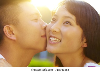 Young Chinese lover holding together in the park