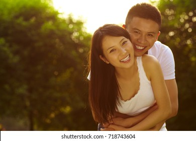 Young Chinese lover holding together in the park smile at camera in the beautiful summer light