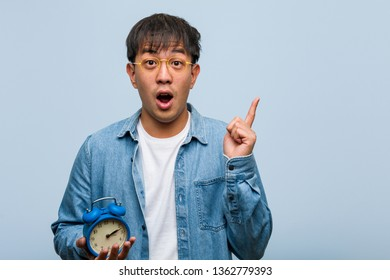 Young chinese man holding an alarm clock having a great idea, concept of creativity