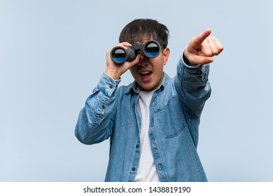 Young chinese man holding a binoculars cheerful and smiling pointing to front
