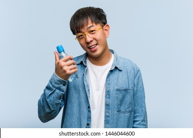 Young chinese man holding a water bottle smiling and raising thumb up