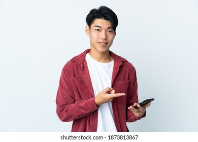 Young Chinese man isolated on white background using mobile phone and pointing it