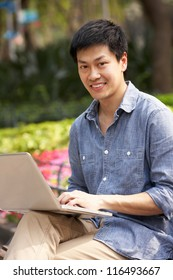 Young Chinese Man Using Laptop Whilst Relaxing On Park Bench