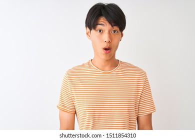 Young chinese man wearing casual striped t-shirt standing over isolated white background afraid and shocked with surprise expression, fear and excited face.
