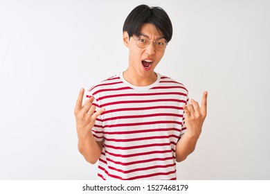 Young chinese man wearing glasses and striped t-shirt standing over isolated white background shouting with crazy expression doing rock symbol with hands up. Music star. Heavy concept.