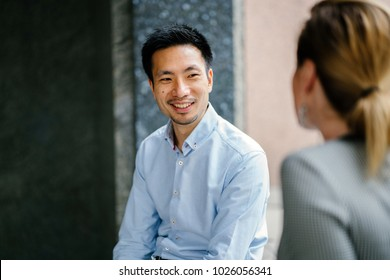 A young Chinese man who is professionally dressed is taking a break and having a discussion with his colleague or team mate in the day. He is smiling and is relaxed and natural.