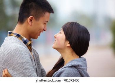young Chinese man and woman holding together