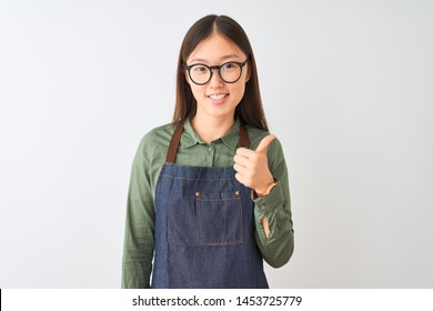 Young chinese shopkeeper woman wearing apron and glasses over isolated white background doing happy thumbs up gesture with hand. Approving expression looking at the camera with showing success.