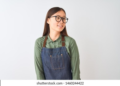 Young chinese shopkeeper woman wearing apron and glasses over isolated white background looking away to side with smile on face, natural expression. Laughing confident.