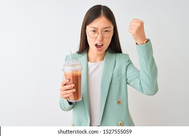 Young chinese woman drinking tomato smoothie over isolated white background annoyed and frustrated shouting with anger, crazy and yelling with raised hand, anger concept