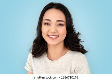 Young chinese woman with hairdo standing isolated on grey background looking camera smiling happy close-up