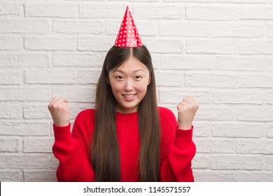 Young Chinese woman over brick wall wearing birthday hat screaming proud and celebrating victory and success very excited, cheering emotion
