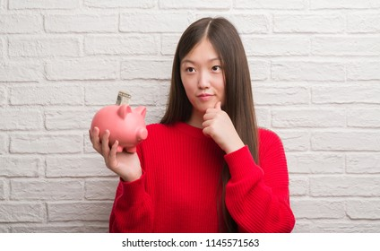 Young Chinese woman over brick wall holding piggy bank serious face thinking about question, very confused idea