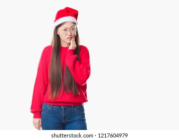 Young Chinese woman over isolated background wearing christmas hat touching mouth with hand with painful expression because of toothache or dental illness on teeth. Dentist concept.