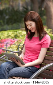 Young Chinese Woman Using Digital Tablet Whilst Relaxing On Park Bench