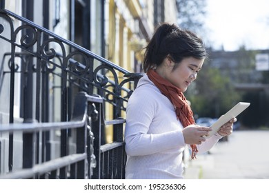 Young Chinese woman using a tablet pc outside and leaning against iron railing fence.
